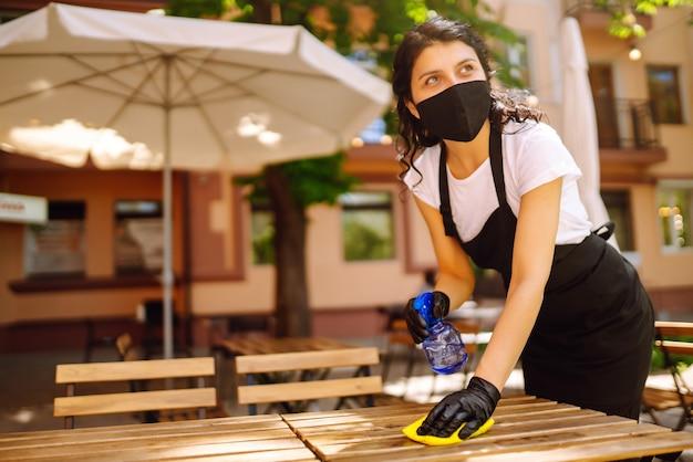 Desinfecção para prevenir covid-19. garçonete limpando a mesa.