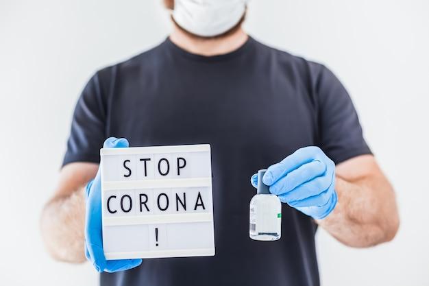 Desinfetante para as mãos, higiene, álcool, gel, frascos e caixa de luz com o texto pare o coronavírus nas mãos de um homem usando luvas médicas de látex e máscara protetora durante as pandemias de coronavírus covid-19. cuidados de saúde