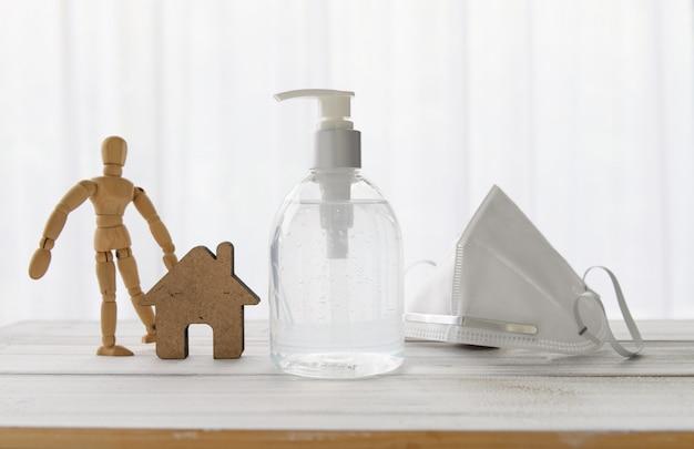 Desinfetante para as mãos, máscara cirúrgica, ícone da casa, boneca de madeira na mesa de madeira com fundo branco macio enquanto a quarentena em casa covid-19.