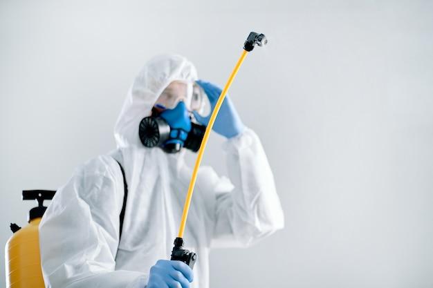 Desinfetante profissional masculino com um frasco de desinfetante. foto com uma cópia-espaço.