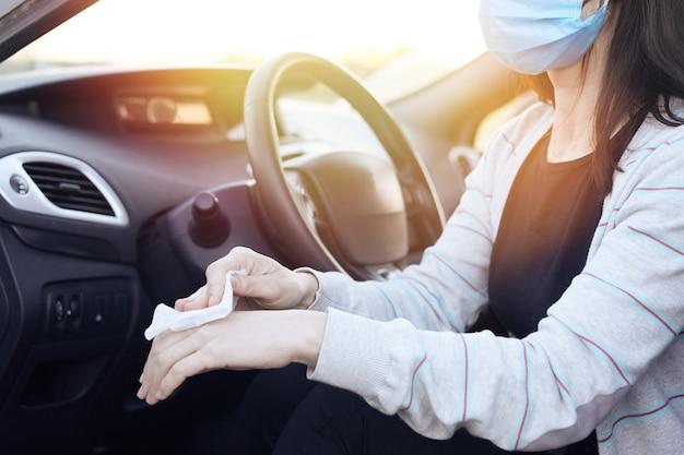 Desinfetante pulverizador manual feminino e toalhetes húmidos anti-sépticos para desinfecção de automóveis.