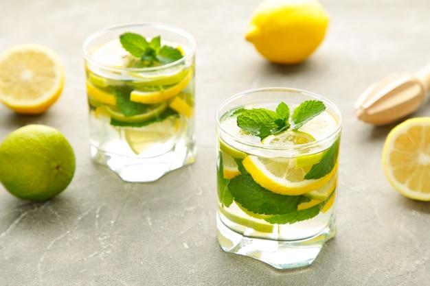 Desintoxicação de água com limão, limão e hortelã em um fundo cinza de concreto