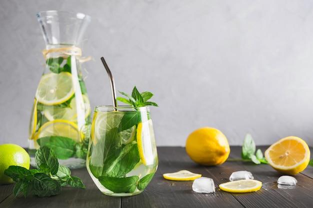 Desintoxicação de água ou limonada com hortelã limão, frutas cítricas em vidro na mesa de madeira e pano de fundo cinzento.
