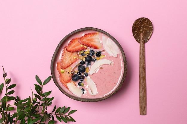 Desintoxicação do corpo - tigela de coco com smoothie de frutas, morangos frescos, mirtilos, chips de coco
