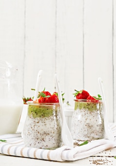 Desintoxicação e saudável superalimentos café da manhã em jar. pudim de sementes de chia de leite de coco vegan com morangos e kiwi.