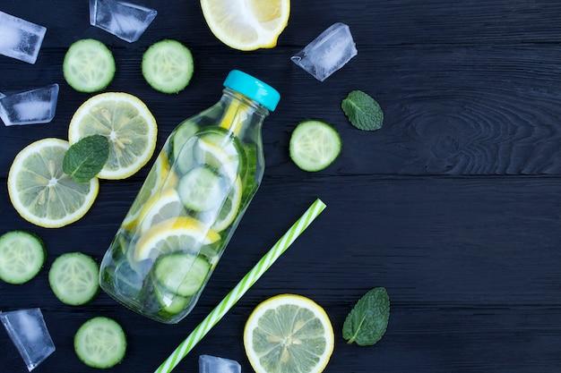 Desintoxicação ou infusão de água com limão, pepino e hortelã na garrafa de vidro