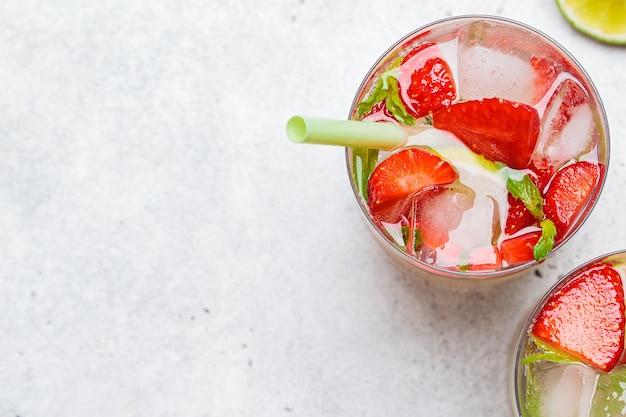 Desintoxicar a água atrevida com morangos e limão em copos, vista superior. conceito de alimentação saudável.