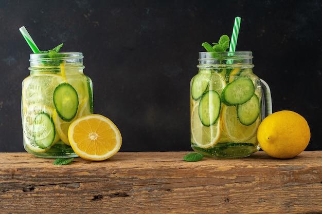 Desintoxicar a água com fatias de limão e pepino em uma jarra no escuro.