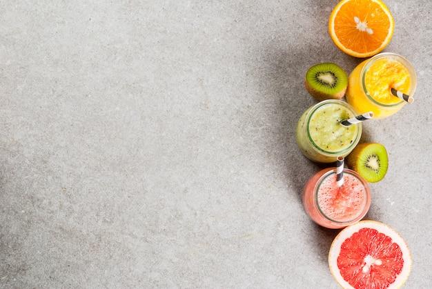 Desintoxicar bebidas de dieta orgânica, smoothies tropicais caseiros - kiwi, laranja, toranja, em frascos repartidos, com ingredientes, sobre uma mesa de pedra cinza. vista superior copyspace