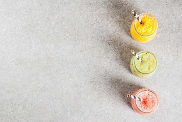 Desintoxicar bebidas de dieta orgânica, smoothies tropicais caseiros - kiwi, laranja, toranja, em frascos repartidos, sobre uma mesa de pedra cinza. vista superior copyspace