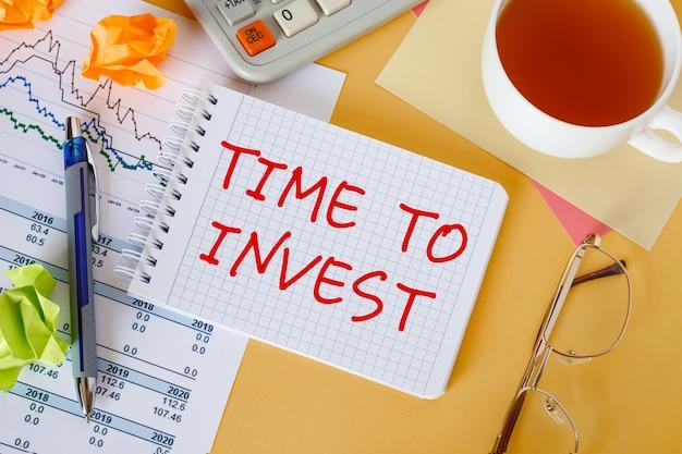 Desktop com documentos, calculadora e bloco de notas. no caderno está a inscrição hora de investir