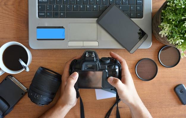 Desktop com equipamento fotográfico, câmera, tripé, flash e computador