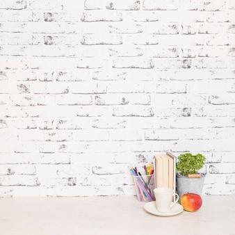Desktop com livros e copo perto da parede