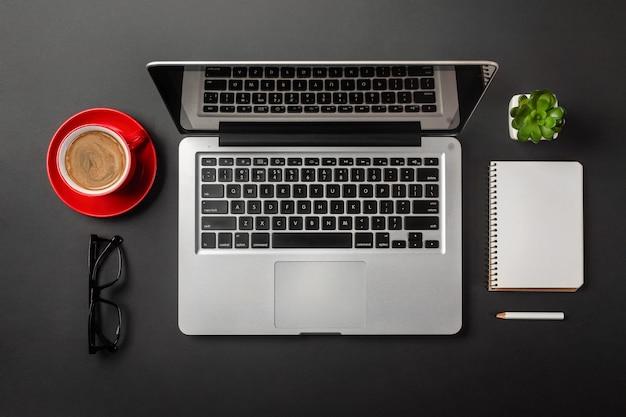 Desktop de escritório elegante preto com laptop e café