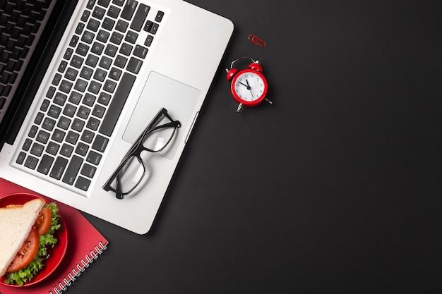 Desktop de escritório preto com notebook e sanduíche para o almoço. vista superior com espaço de cópia.
