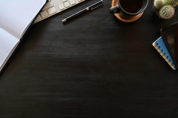 Desktop de madeira escuro da vista superior com acessórios do escritório e espaço da cópia.