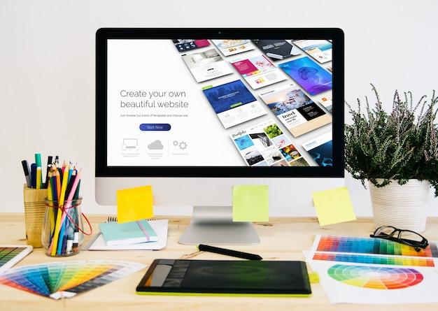 Desktop de papelaria com material de design, computador e tablet gráfico