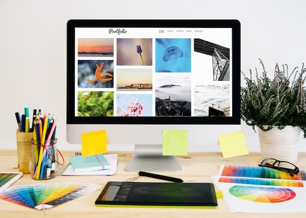 Desktop de papelaria com material de design, computador e tablet gráfico.