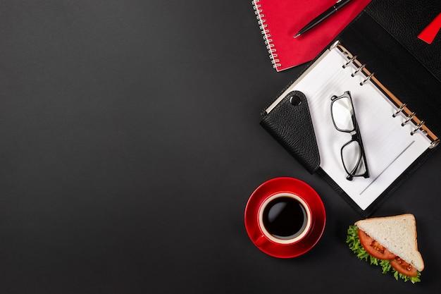 Desktop elegante escritório preto com laptop, xícara de café e um sanduíche para o almoço em vista superior