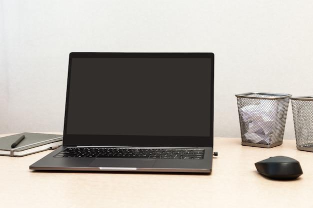 Desktop para estudante ou freelancer. espaço de trabalho. local de trabalho com cinza moderno laptop, caderno e mouse de computador na mesa de luz. copie o espaço.