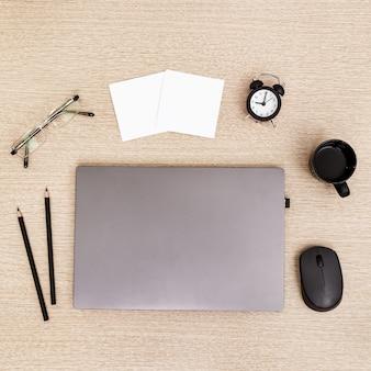 Desktop para estudante ou freelancer. espaço de trabalho. local de trabalho com laptop moderno cinza, xícara de café, copos e relógio para controle de tempo na mesa de luz. postura plana.