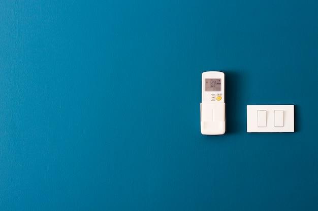 Desligue - ligue e controle remoto do ar na parede azul