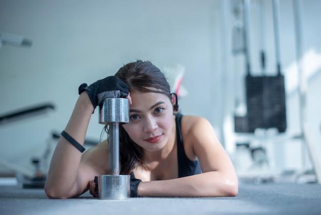 Deslize a ideia da mulher da aptidão que exercita com elevador o peso no gym.