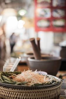 Deslize a papaia para os ingredientes da salada da papaia com almofariz do borrão. comida de rua na tailândia.
