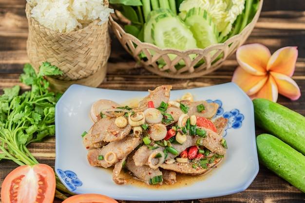 Deslize a salada grelhada da carne de porco com arroz pegajoso e muito vegetal no fundo de madeira da tabela.