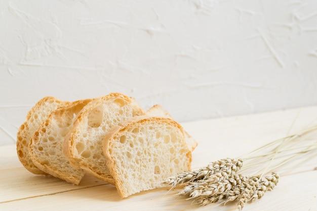 Deslize o pão e o trigo na madeira larga
