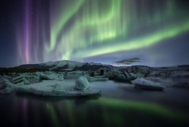 Deslumbrante aurora boreal sobre o lago glaciar jokulsarlon, islândia