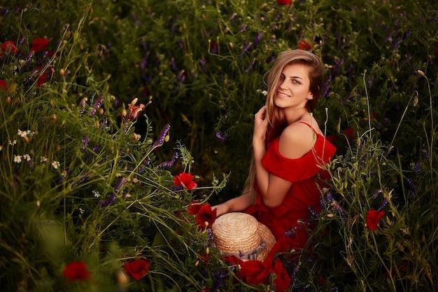 Deslumbrante jovem vestido vermelho senta-se no campo verde com papoilas vermelhas