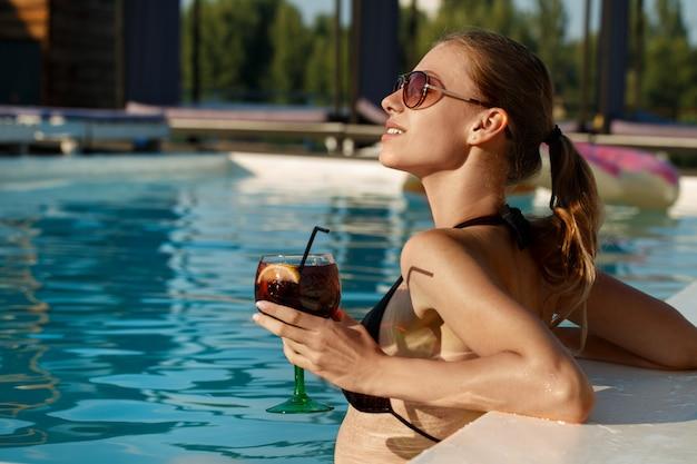 Deslumbrante mulher jovem e bonita se bronzear na piscina com uma bebida na mão