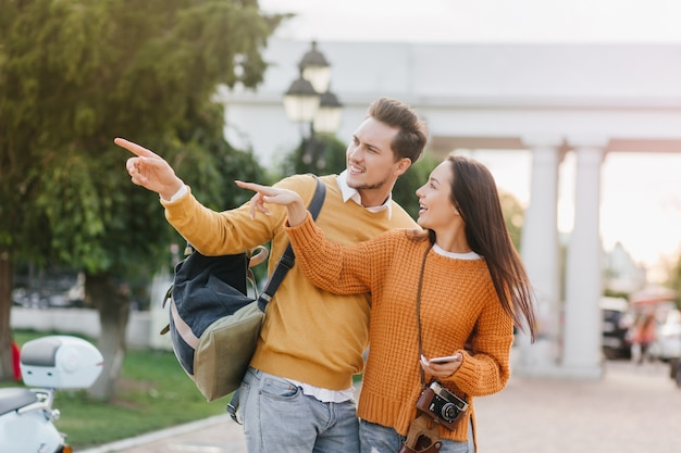 Deslumbrante turista feminina segurando um smartphone e falando com um homem