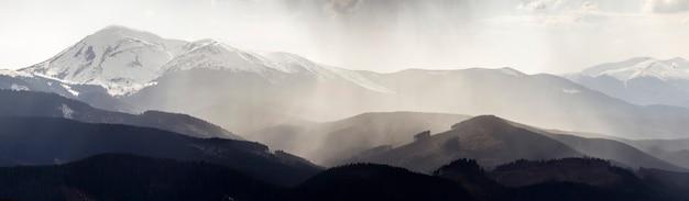 Deslumbrante vista panorâmica das magníficas montanhas nebulosas dos cárpatos, cobertas por uma floresta sempre verde na manhã enevoada e tranquila ou à noite sob o céu escuro e nublado. montanhas cobertas de neve no topo da distância.