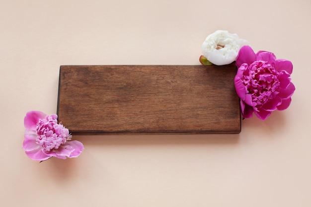 Deslumbrantes lindas peônias rosa e brancas com placa de madeira