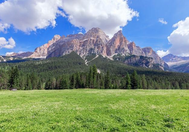 Deslumbrantes vistas panorâmicas sobre o pitoresco prado alpino no sopé da montanha.