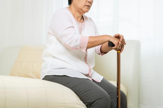 Desmaiar, dor de cabeça, estresse de mulher velha com vara, problema de saúde do conceito sênior