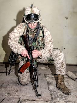 Desmontagem, conserto e manutenção de fuzileiros navais de carabina automática de assalto em condições de combate. lutador do esquadrão anti-terrorista verificando e neutralizando armas ilegais encontradas durante o ataque
