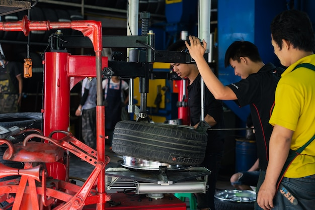 Desmontagem de mecânico ou técnico de automóveis não identificado e verificação de uma roda de liga de cromo de carro