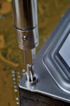 Desmontagem de um disco rígido de computador usando uma chave de fenda para diagnosticar e reparar problemas