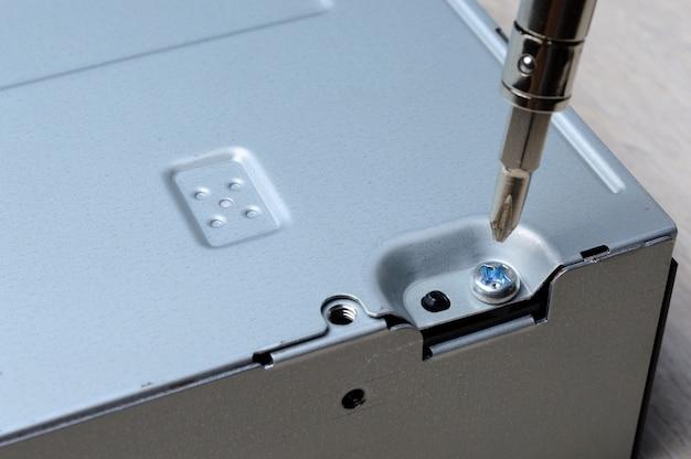 Desmontagem de uma caixa de metal de computador com uma pequena chave de fenda. fechar-se