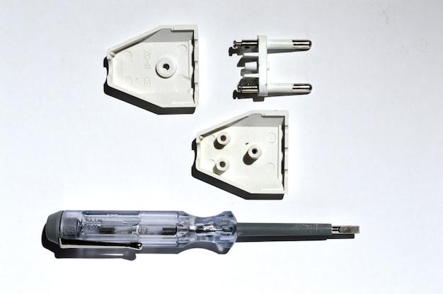 Desmontagem do plugue elétrico usando um testador de chave de fenda. no fundo branco