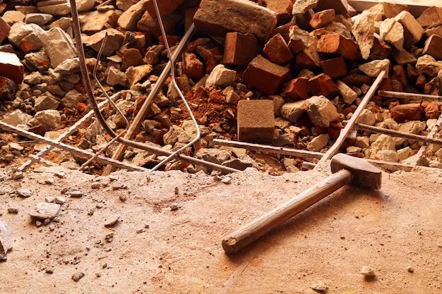 Desmontando, desmontando o chão. piso de concreto e tijolos quebrado. destruindo a superfície de concreto. renovação, prédio antigo, construção.