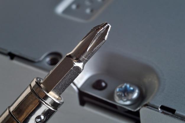 Desmontando uma caixa de metal do computador com uma pequena chave de fenda