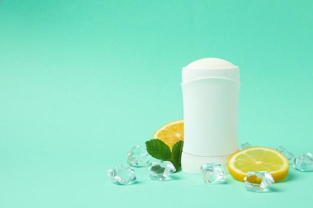 Desodorante corporal, gelo e limão em fundo de hortelã, espaço em branco para texto