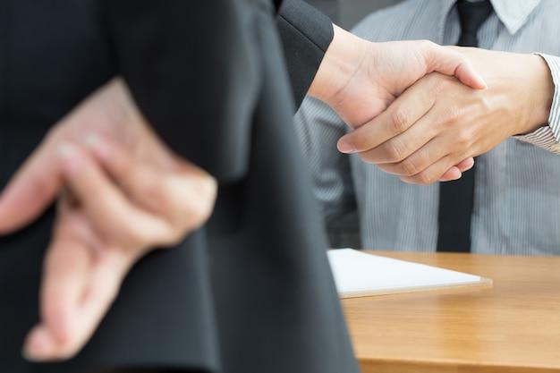 Desonestidade, conceito de fraude de negócios, empresário mostrando os dedos cruzados