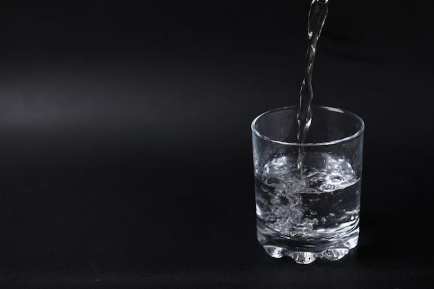 Despejando água em um copo meio cheio.