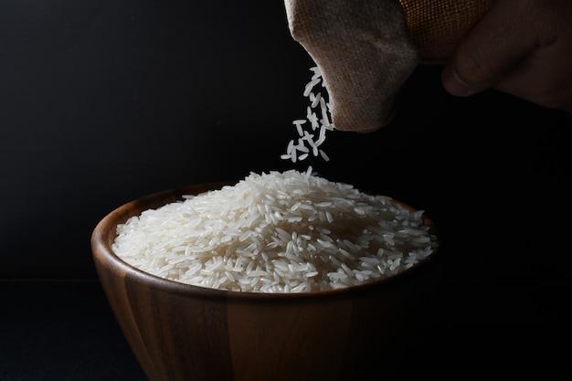 Despejando arroz jasmim em uma tigela de madeira em fundo preto
