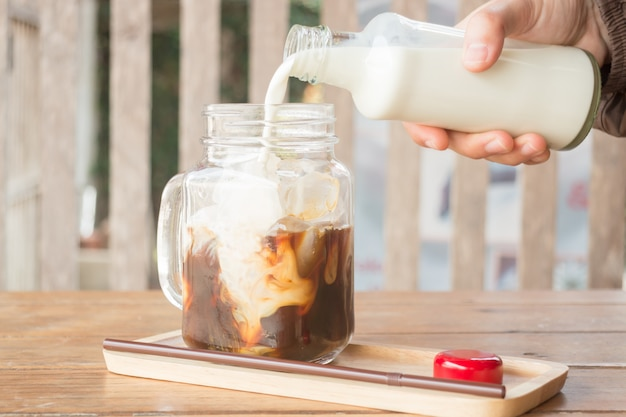 Despejando leite ao copo gelado de café